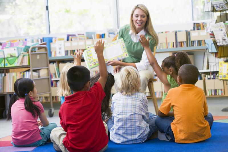 Blond teacher teaching young girls and boys